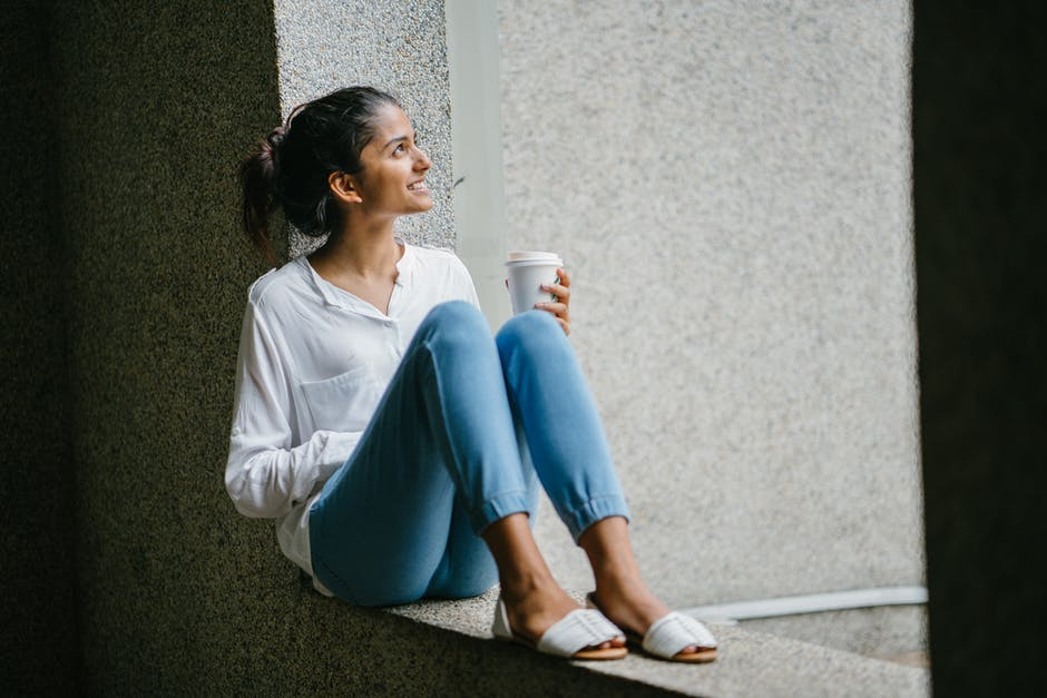 A woman sitting in front of a building